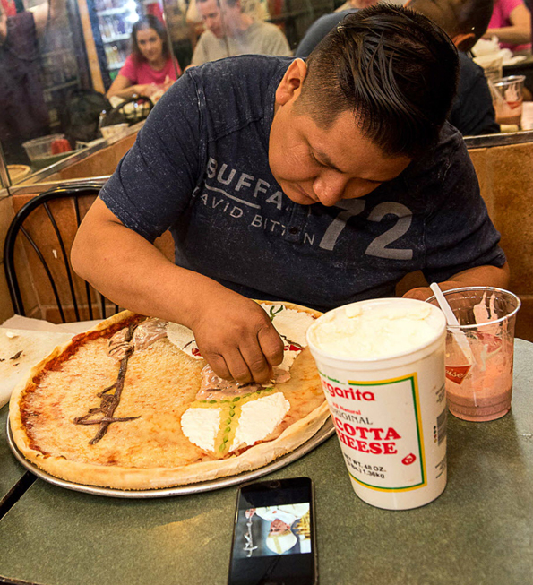 NEW YORK - September 21: PULSE - Alex Flores making a portrait of Pope Francis on a pizza with pizza toppings at BLEECKER STREET PIZZA, 69 7th Avenue South in Manhattan. September 21, 2015. (Photo by Gabi Porter)